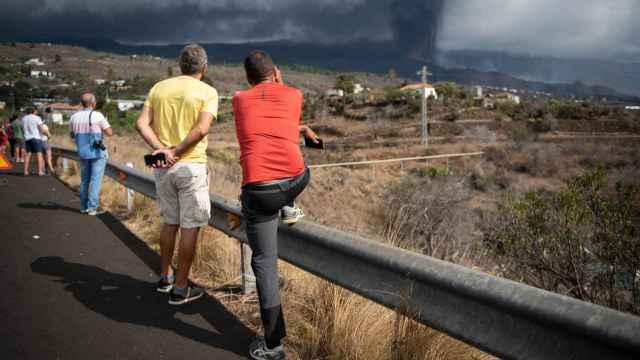 Algunos curiosos se agolpan en el arcén para ver el volcán este sábado.
