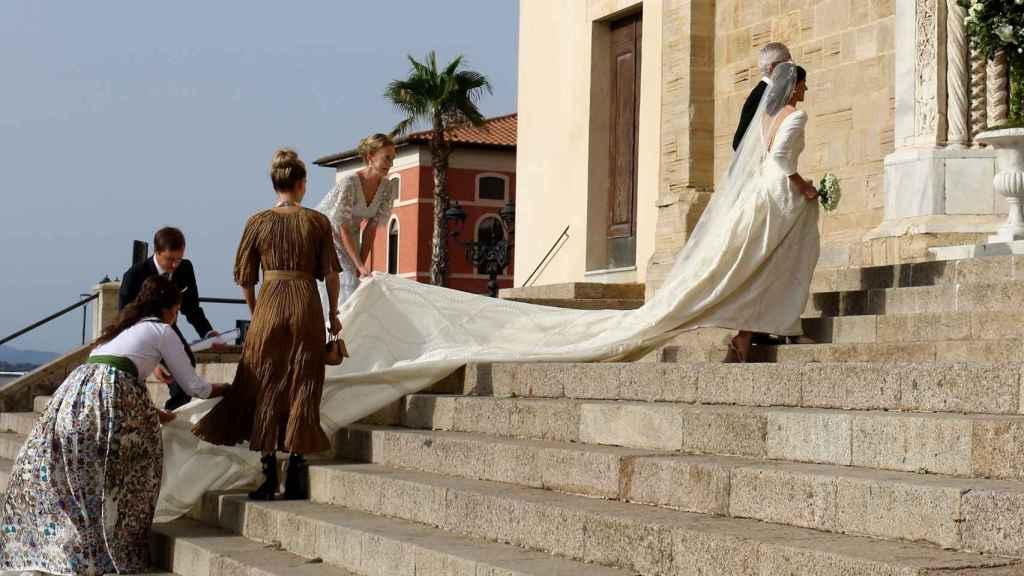 La novia necesitó ayuda con la cola de su traje para subir las escaleras hacia el templo.