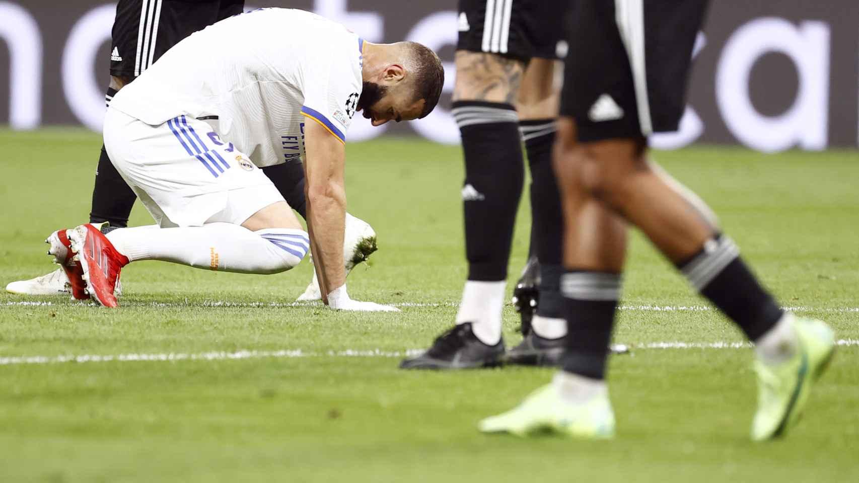 Karim Benzema agachado mira al césped