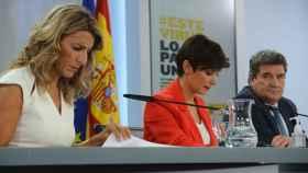 Yolanda Díaz y José Luis Escrivá, separados por la portavoz, Isabel Rodríguez, en la sala de prensa de Moncloa.