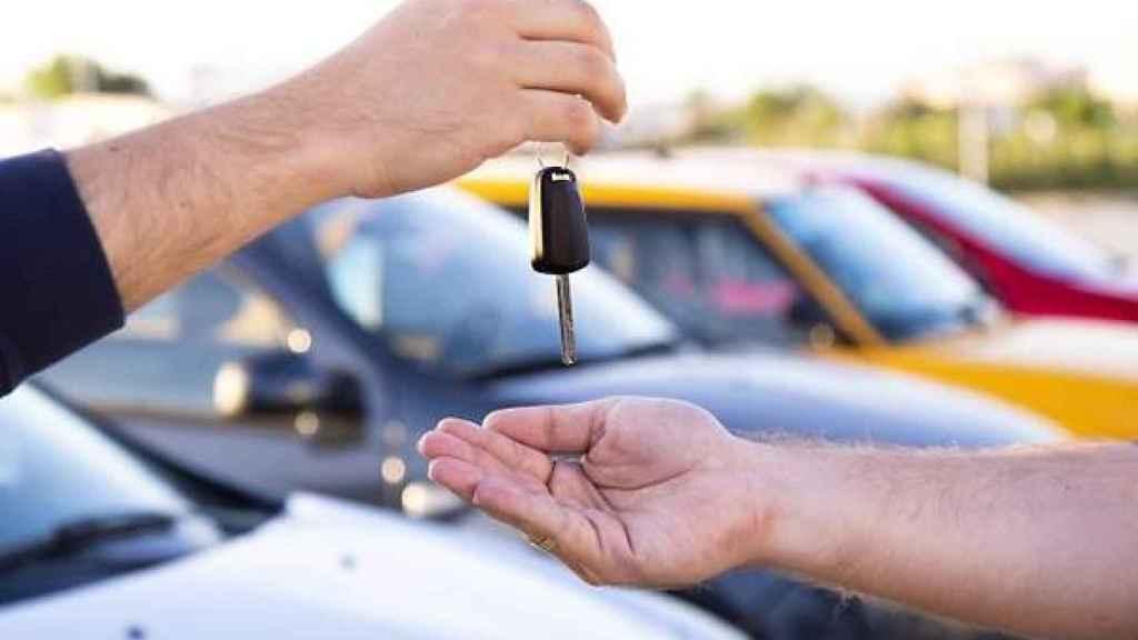 Dos personas intercambiándose las llaves del vehículo