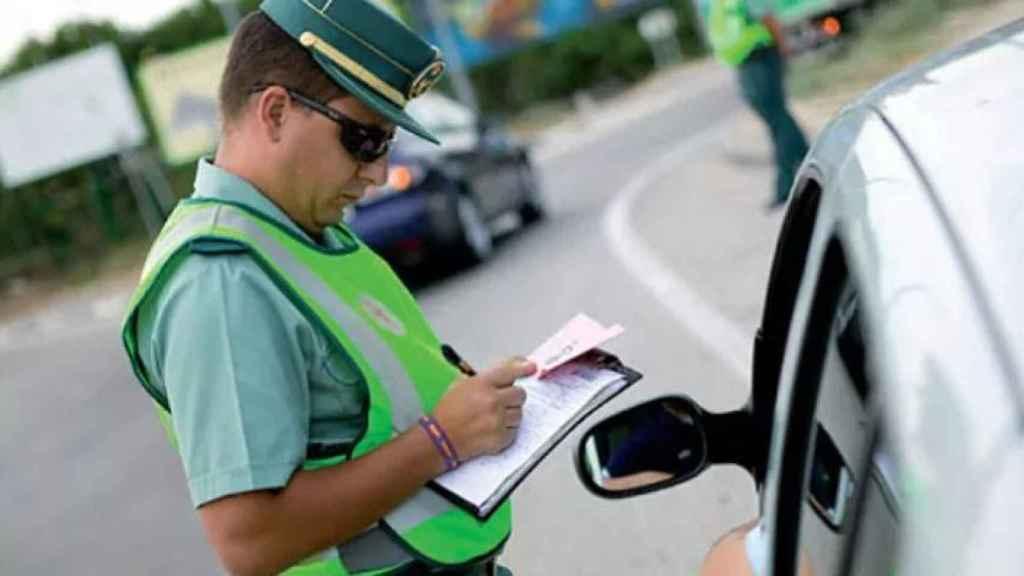 Un guardia civil pone una multa de tráfico.