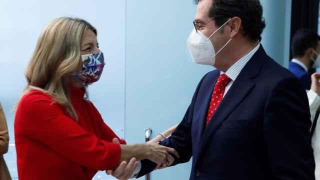 Yolanda Díaz, saluda con las dos manos al presidente de la CEOE, Antonio Garamendi.