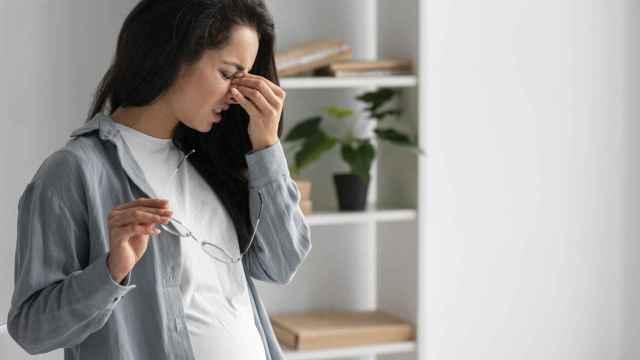Una mujer embarazada se quita las gafas.