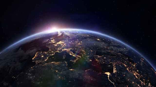 El Sol asoma ligeramente tras el planeta Tierra.