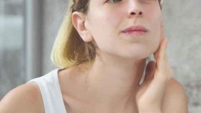 Chica aplicando producto cosmético en el rostro.