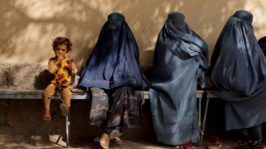 Una niña junto a tres mujeres cubiertas por burkas sentadas afuera de un hospital de Kabul, Afganistán.