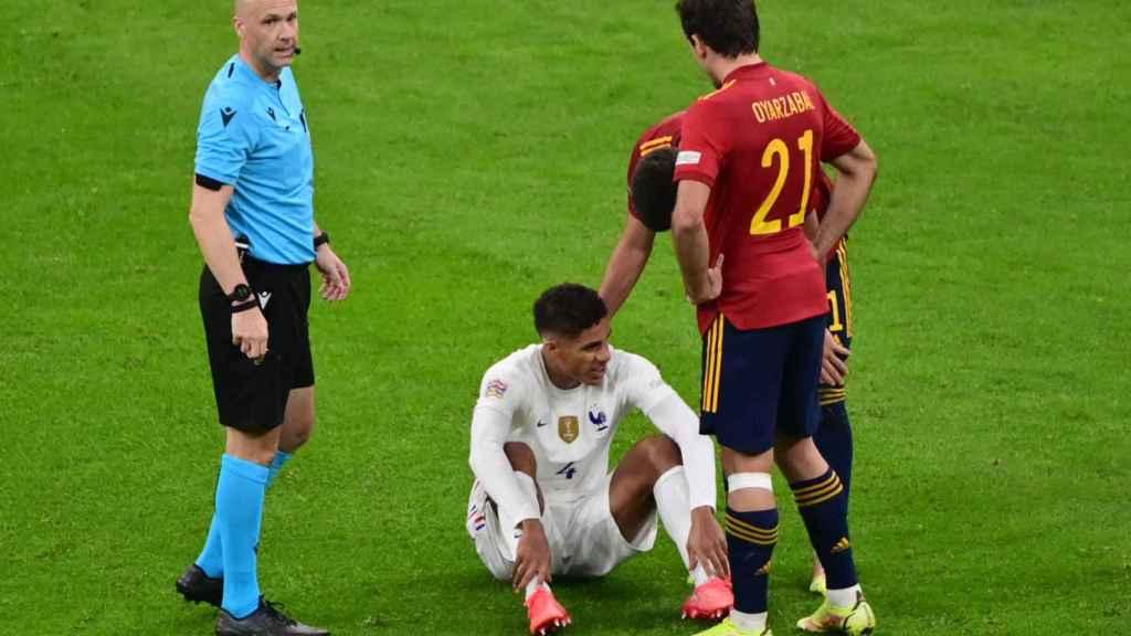 Raphael Varane se tira al suelo lesionado durante el España - Francia