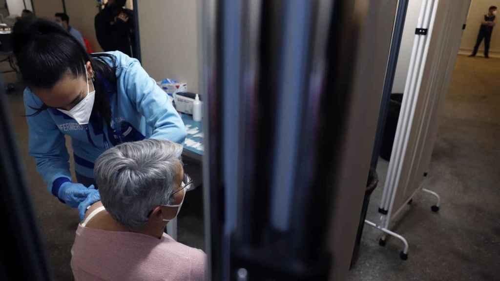 Una enfermera vacuna a una mujer en España.