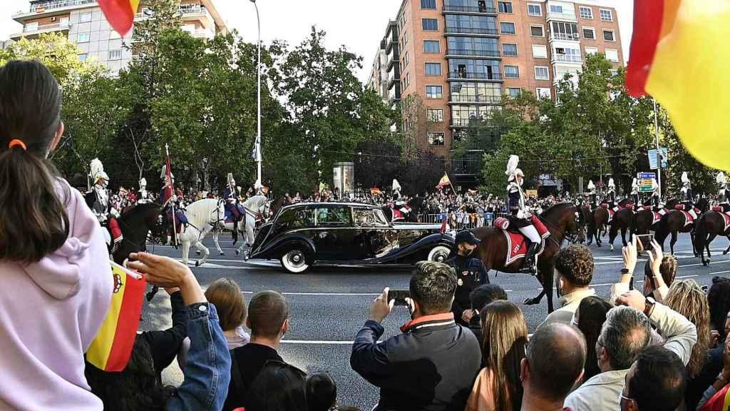 El coche oficial con los reyes Felipe y Letizia pasa por las calles del centro de Madrid.