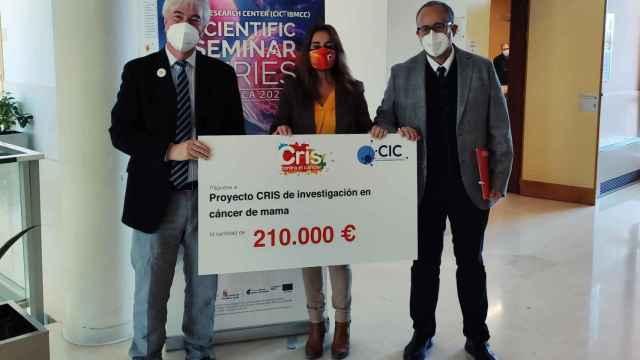 Atanasio Pandiella, Marta Cardona y José Miguel Mateos muestran el cheque de 210.000 euros donados por la Fundación CRIS a los investigadores del CIC salmantino