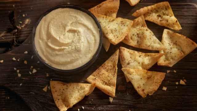 Un cuenco con hummus con chips para mojar.