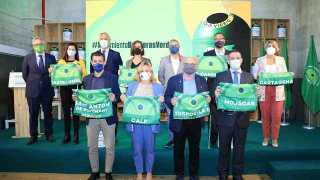 Los ediles de los ocho municipios posan con sus banderas verdes durante la ceremonia organizada ayer por Ecovidrio.