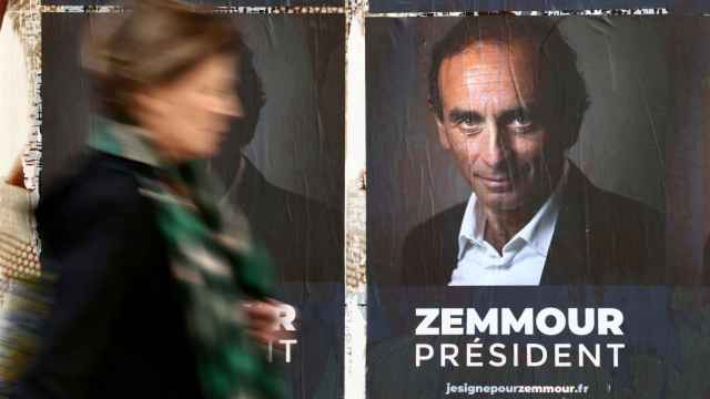 A woman walks past posters in support of French far-right commentator Eric Zemmour in Paris