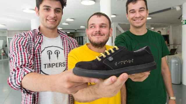 De izquierda a derecha: Aitor Carratalá, Diego Soliveres y Roberto Mohedano, cofundadores de Timpers, muestran una de sus zapatillas con el nombre de la marca bordado en Braille.