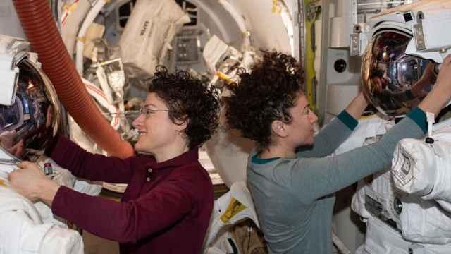 Las astronautas de la NASA Christina Koch y Jessica Meir trabajan en sus trajes antes de una caminata espacial.