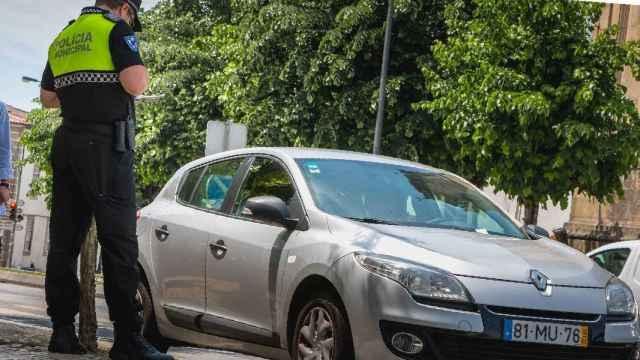 Un policía municipal multa a un coche estacionado.
