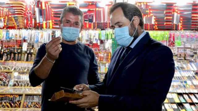 Paco Núñez recibe la navaja que le han regalado los vendedores ambulantes.