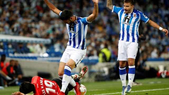 Los jugadores de la Real Sociedad pelean un balón con un rival del Mallorca en el suelo