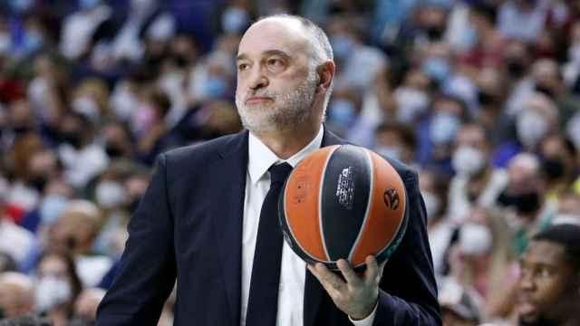 Pablo Laso en el banquillo del Real Madrid con el balón en la mano