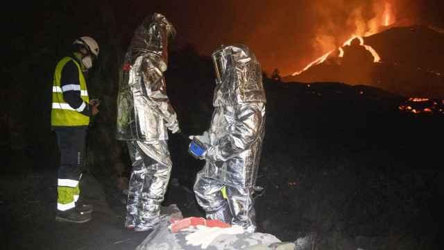 Los especialistas que visitan la erupción volcánica cada noche vestidos de astronautas.