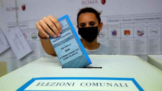 Una mujer deposita su voto en una urna en Roma.