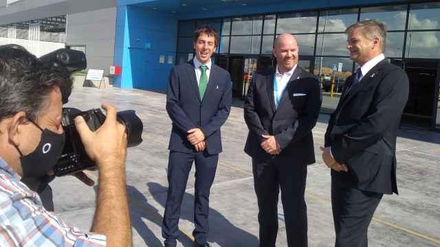 Víctor Romía, Will McLean, y Fred Pattje , en la fachada del nuevo centro logístico Amazon Robotics.