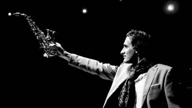 Un músico saluda al público alzando su saxofón