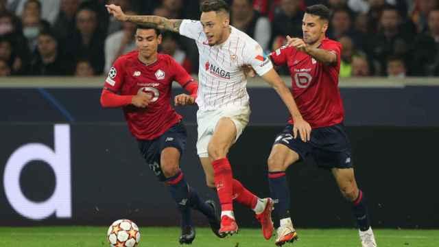 Lucas Ocampos se lleva el balón ante la presión de Zeki Celik y Benjamin André, en el Lille - Sevilla