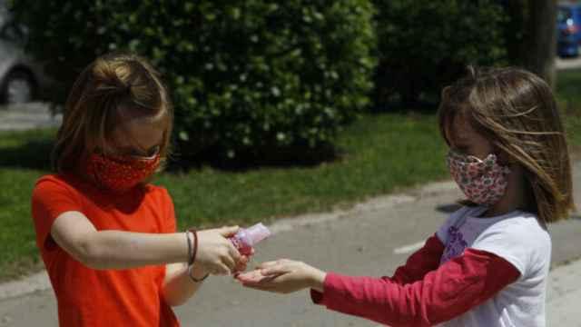 Dos niñas con mascarillas se lavan las manos con gel desinfectante.