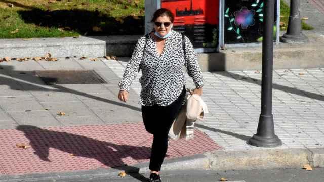 Una mujer con mascarilla cruza el paso de peatón de La Farola