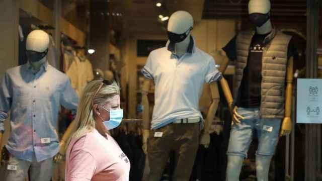 Un mujer pasa delante de una tienda de ropa.