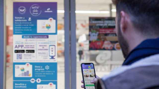Un cliente utiliza la plataforma de la startup en la puerta en un supermercado para contribuir con su donación digital de alimentos a ayudar a los más vulnerables.