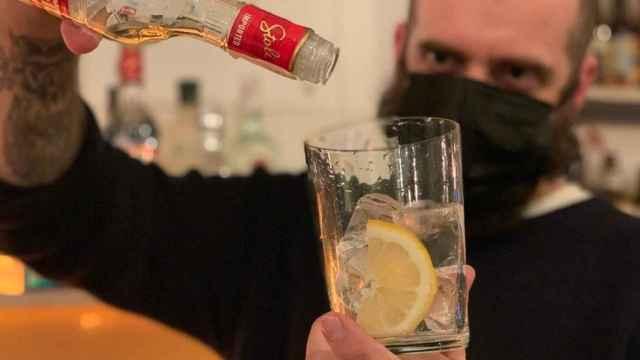 Sergio Ramírez, camarero en Madrid, sostiene una botella de alcohol vacía .