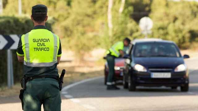 Dos agentes de la Guardia Civil sancionando a un conductor.