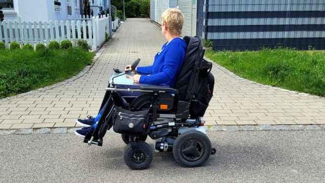 Una mujer pasea en su silla de ruedas.
