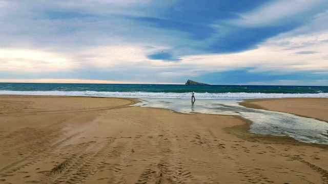 Una persona hace deporte por la playa frente a la Illa de Benidorm.