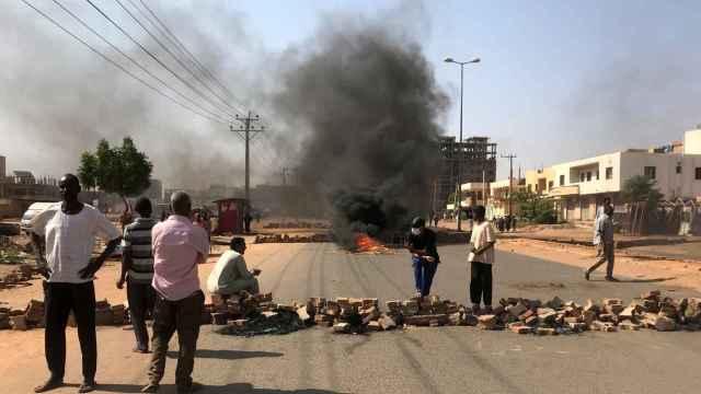 Manifestantes sudaneses levantan una barricada en una carretera de Jartum.