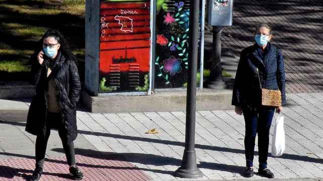 Dos mujeres con mascarilla esperan en el paso de peatón de La Farola